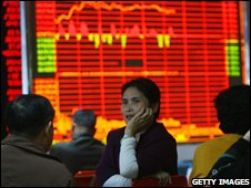 Investors view stock prices at a securities company in Chongqing, China