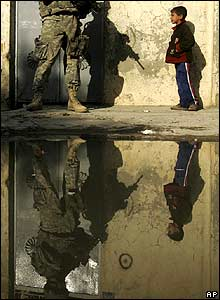 A US soldier meets a little boy on patrol in Mosul, Iraq