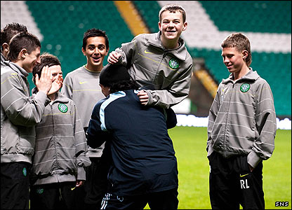 Young Celtic player Adam Brown is held aloft by Maradona after he found Fernando Gago's lost St Christopher medallion on the pitch