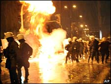 A Molotov cocktail burns in front of police outside the US embassy in Athens on 17 November 2008