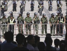 Chinese police officers stand guard as hundreds of workers gather outside a government building after a large toy factory closed in Guangdong province, southern China, on 17 October 2008