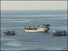 British naval vessels intercept a suspected pirate dhow in the Gulf of Aden