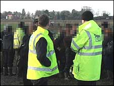 Gangmasters Licensing Authority officers look on as workers are interviewed