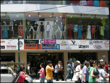 Shoppers pass a clothing store in Peru