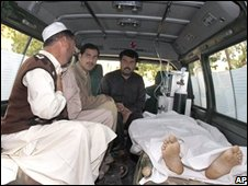 Relatives sit beside the body of the retired general's driver