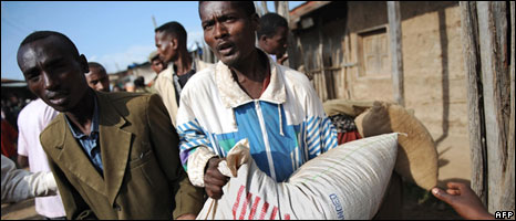 Ethiopian residents receive a sack of food aid at a distribution centre