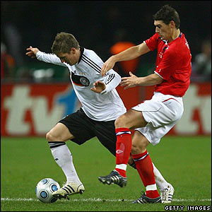 Bastian Schweinsteiger shadows the ball from England's Gareth Barry