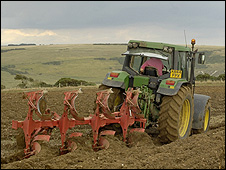 A farmer ploughs a field in East Sussex, UK