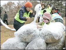 Activists tie plastic bags containing leaflets condemning North Korean leader Kim Jong-il on 20 November