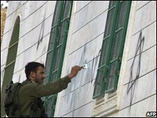 Israel soldier painting over graffiti on Hebron mosque