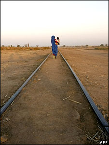 Sudanese internally displaced woman carries her child as she walks along railway tracks in Kalma camp
