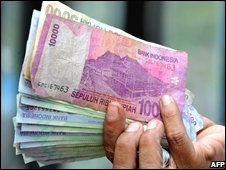 A man holds Indonesian rupiah notes in Jakarta (20/11/2008)