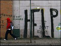 """Joven pasa frente a un grafiti que dice """"AYUDA"""" en una pared de Detroit"""