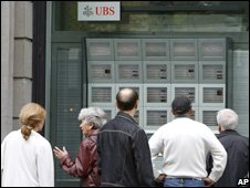 People look at stock market quotes at a branch of the UBS bank in Zurich, Switzerland (file photo)