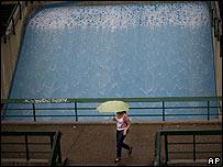 Una mujer camina, bajo la lluvias, cerca de una fuente.