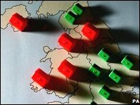 Monopoly house pieces on a map of the UK