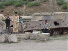 Children play on a crippled Soviet tank in Kabul 
