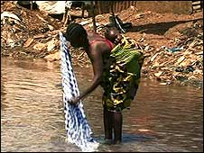 Woman washing clothes in Freetown river