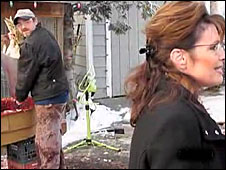 A still from the video of Sarah Palin with a turkey slaughter man in the background. Full video on Anchorage Daily News website