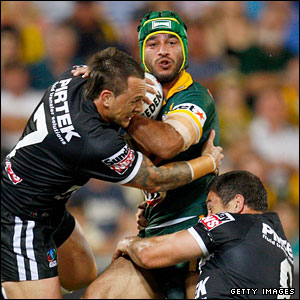 Johnathan Thurston is tackled by two Kiwis