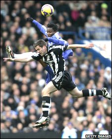 Michael Owen battles for the ball in the air for Newcastle