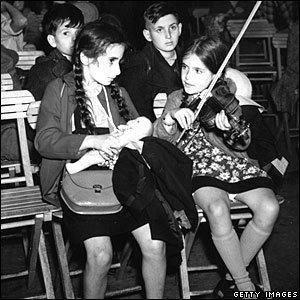 A young girl from Berlin plays violin to her friend at London's Liverpool Street station