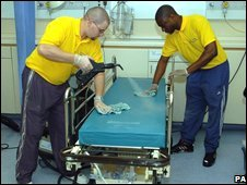 Contractors steam clean hospital beds