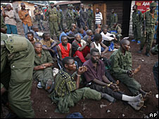 Congolese men cuffed by troops sit at a checkpoint in Kibati, 23 November 2008