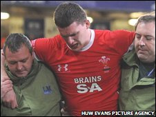 Ian Evans is helped from the Millennium Stadium pitch after being injured
