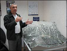 Alexander Belokobylsky stands by the model of a ski resort