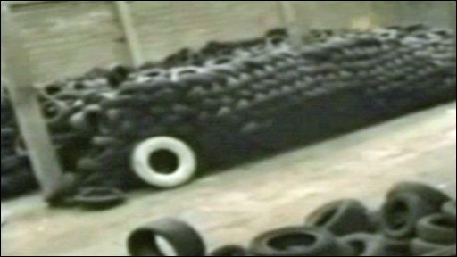 Piles of dumped tyres in warehouse