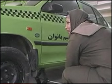 A Women's Taxi driver changes a tyre in Tehran