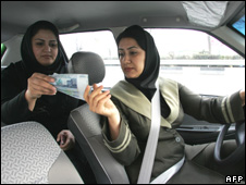 A woman pays the driver in Tehran