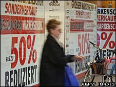 A woman walks past a storewindow advertisement showing drastic price reductions in Berlin