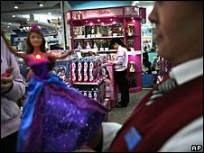 A Chinese employee sets up a Barbie doll on a pedestal for display at a toy store in Beijing