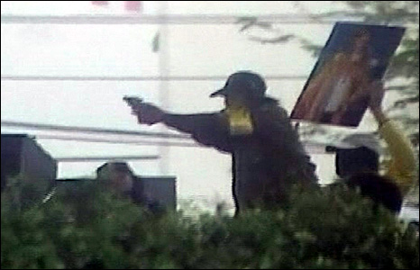 PAD supporter fires at pro-government activitists in Bangkok, whilst another holds up a picture of the king (Image courtesy of TPBS)