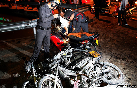 Police inspect motorbikes set alight by anti-government protesters in Bangkok