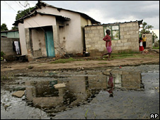 A child walks past rain water and sewage near Harare (25 November 2008)
