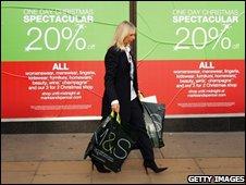 Shopper walking past M&S sale signs