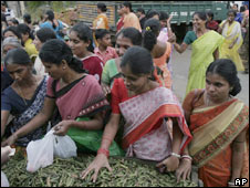 Workers of a garment factory buy vegetables as they leave work in Bangalore