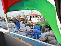عمال يحملون أطنانا من الغذاء على متن سفينة ليبية متوجهة الى قطاع غزة