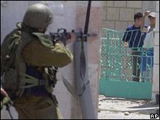 Israeli soldier pointing gun towards Palestinians