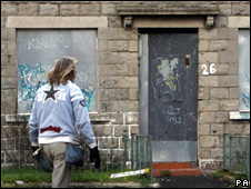 Man walks past boarded up flats in Glasgow