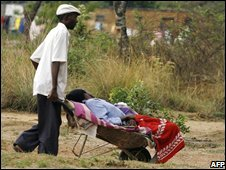 A Zimbabwean man pushes his ill relative to a cholera clinic in Harare, 25 November, 2008