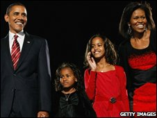 US President elect Barack Obama stands on stage along with his wife Michelle and daughters Malia (red dress) and Sasha (black dress) at a election night gathering in Grant Park (November 4, 2008)