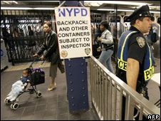 File photo of a police officer watching commuters in a New York subway station, October 2005