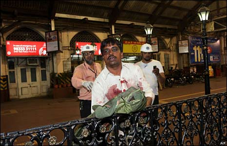 An injured man leans on a railing after one of the attacks in Mumbai