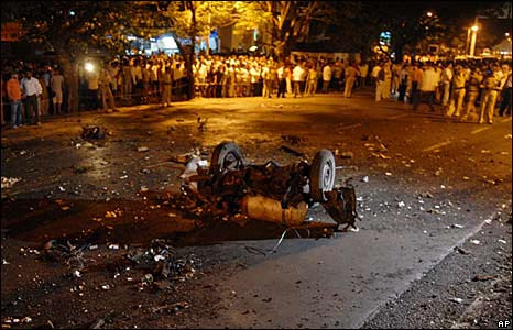 People stand around a damaged vehicle at the site of an explosion in Mumbai