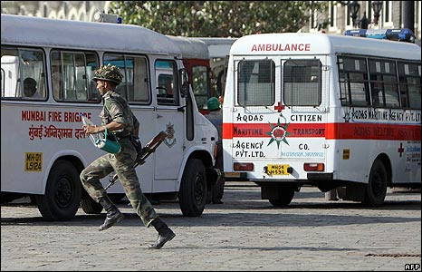 An emergency worker runs past ambulances outside the Taj Mahal hotel in Mumbai, India