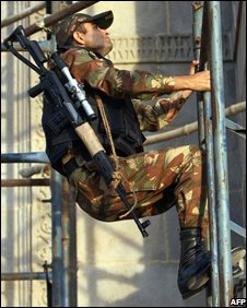 Indian army snipers climb scaffolding opposite the Taj Mahal Palace hotel